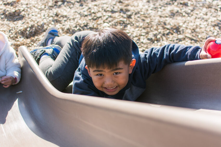 Gabriel playing on the slide at the park