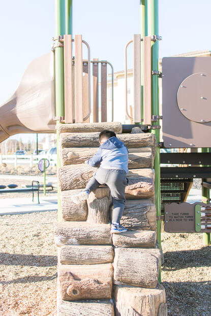 Gabriel climbing the logs at the park