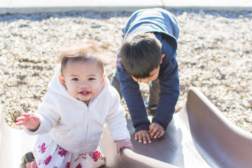 Gabriel and Emilia playing on the slide