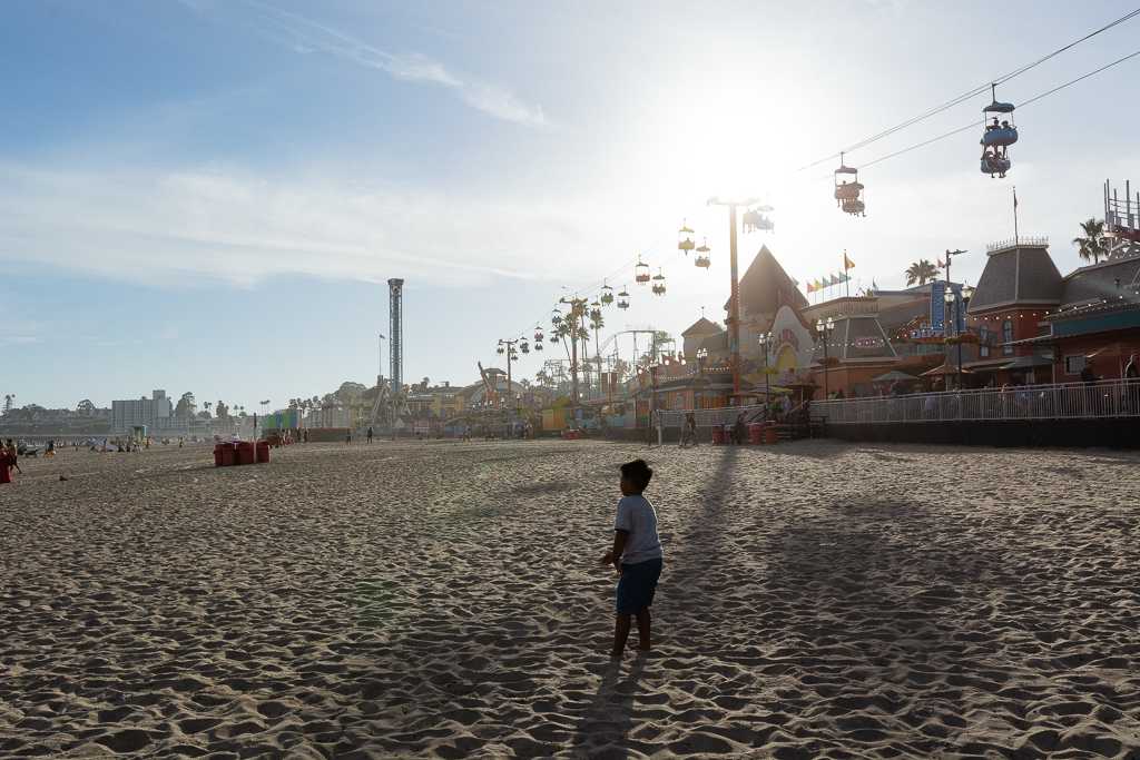 Gabe playing on the sand at Santa Cruz Beach Boardwalk at Sunset